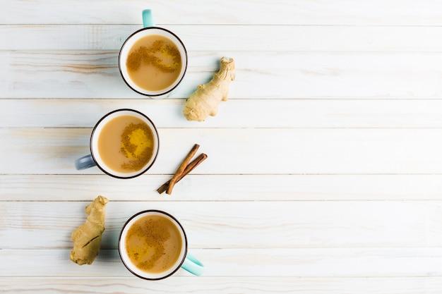 Herbata masala w ceramicznych kubkach z zimowymi przyprawami cynamonu i imbiru