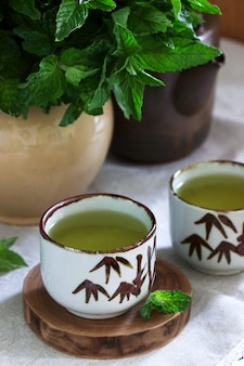 Herbata miętowa w klasycznym chińskim zestawie herbacianym i bukiet mięty w dzbanku