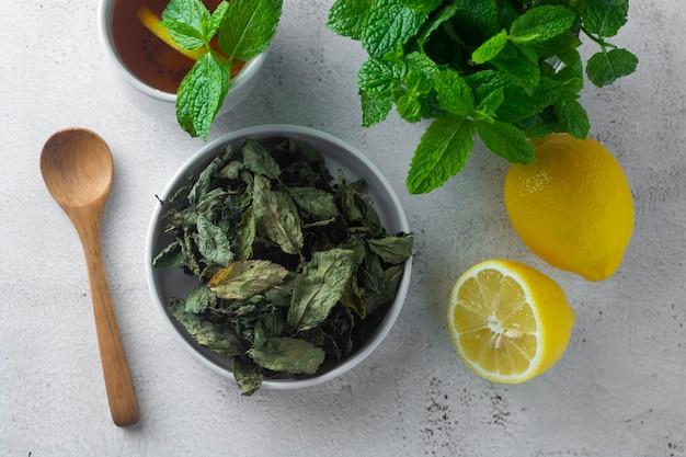 Herbata miętowa, wytrawne liście mięty na łuku, na jasnej powierzchni, na białym tle,
