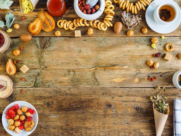 Herbata na starym stole. zioła i słodycze. na środku stołu miejsce na napisy.