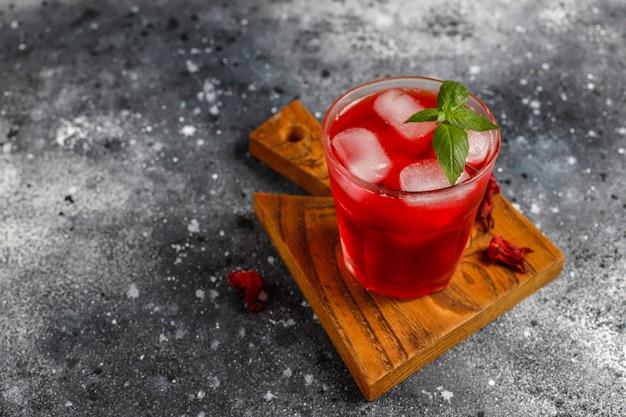 Herbata na zimno z hibiskusa z lodem i liśćmi bazylii.