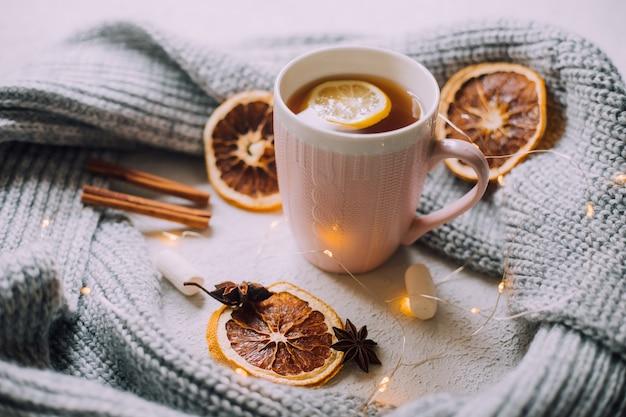 Herbata noworoczna z girlandą i pomarańczami. świąteczny nastrój. zimny wieczór. gorące napoje.