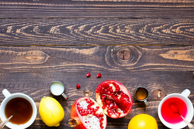Herbata owocowa z cytryną, mlekiem, miodem, pomarańczą, granatem, na drewnianym tle