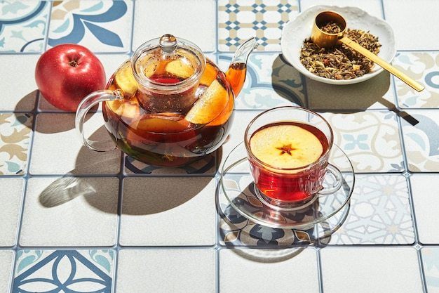 Herbata owocowa z jabłkami i tymiankiem w szklanym czajniczku i filiżance na stole z kolorowych płytek