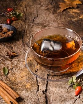 Herbata pod wysokim kątem w szkle z cynamonem na drewnie
