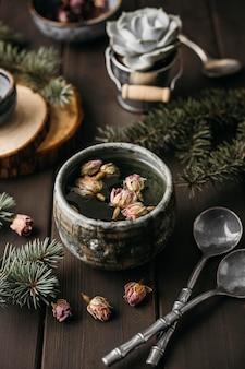 Herbata pod wysokim kątem z suszonymi kwiatami w rustykalnym kubku z łyżeczkami