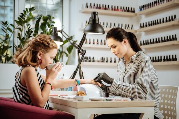 Herbata podczas manicure. stylowa nastolatka noszenie akcesoriów i pasiastej sukni picia herbaty podczas manicure