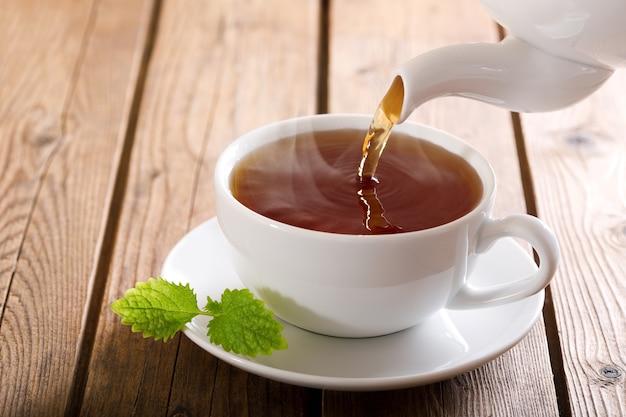 Herbata przelewa się z imbryka do filiżanki