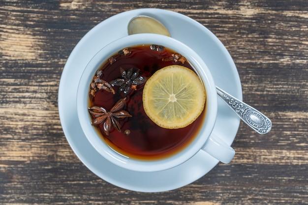 Herbata przyprawowa składająca się z cynamonu, czarnego pieprzu, kardamonu, anyżu gwiazdkowatego, cytryny, goździków i gorącego soku jabłkowego. zbliżenie, widok z góry. herbata cynamonowa. napój herbaciany