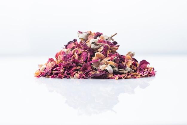 Herbata sucha kwiat róży na białym tle na białym tle, zbliżenie