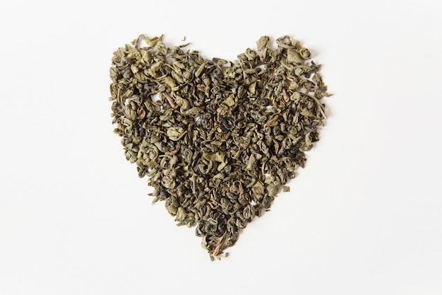 Herbata sucha zielona w kształcie serca. białe tło. widok z góry