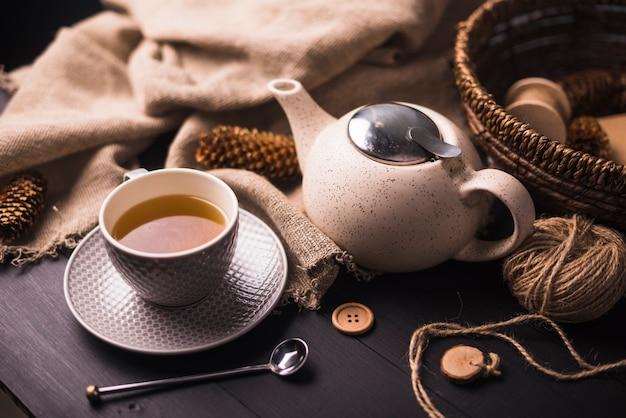 Herbata; szyszka; czajniczek; przycisk; worek i wiklinowy koszyk na stole