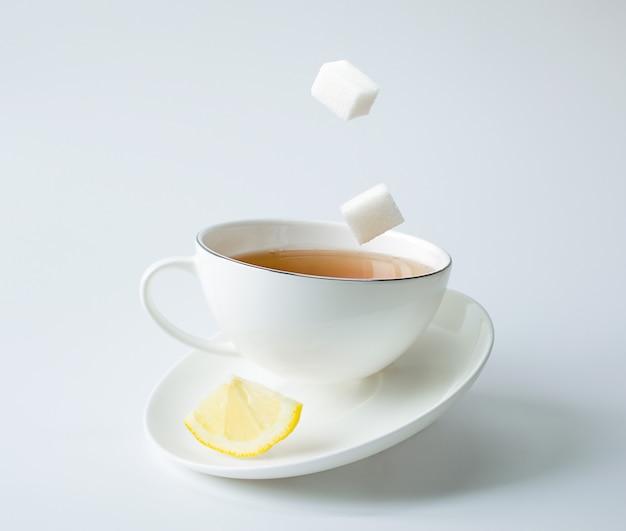 Herbata w białej filiżance z cytryną i cukrem. równowaga i lewitacja.
