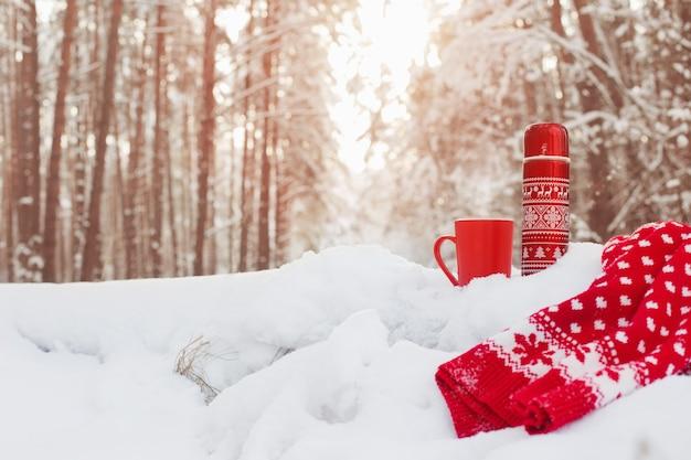 Herbata w czerwonym termosie w zimowym lesie