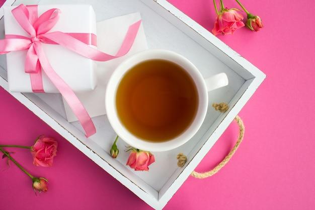 Herbata w filiżance i prezent na białej drewnianej tacy na różowym tle odgórny widok.