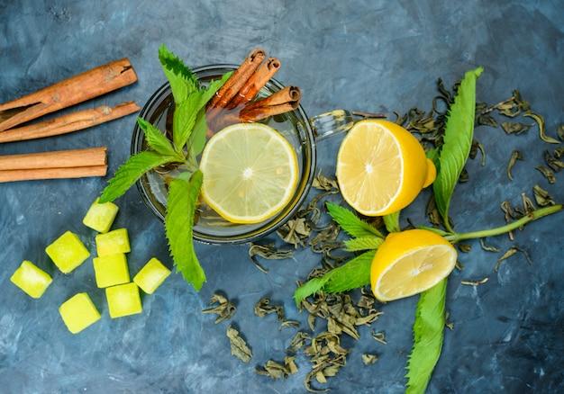 Herbata w filiżance z cytryną, miętą, laski cynamonu, kostki cukru widok z góry na niebieskiej powierzchni