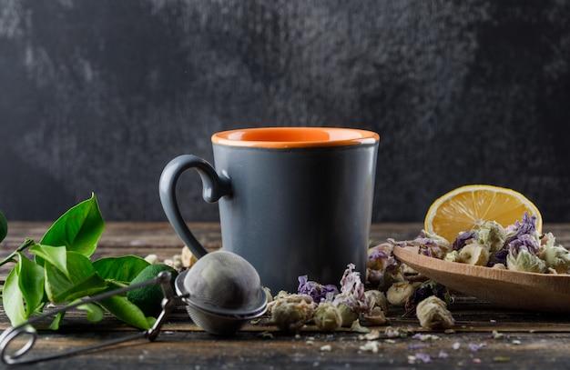 Herbata w filiżance z limonkami, sitkiem, ziołami, cytryną, limonkowym widokiem z boku na ciemnej i drewnianej powierzchni