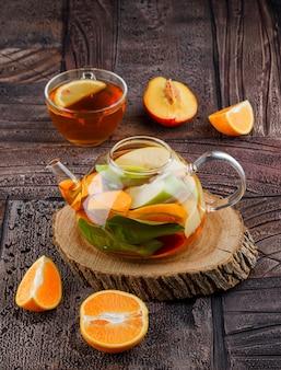 Herbata w filiżance z owocami, drewniany kawałek wody z owocami