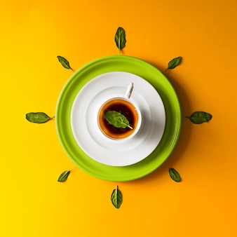 Herbata w filiżance z zielonymi liśćmi na pomarańczowej ścianie. pojęcie czasu.