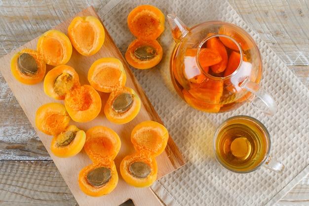 Herbata w imbryku i kubku z morelami, deska do krojenia płasko ułożona na drewnianym ręczniku kuchennym
