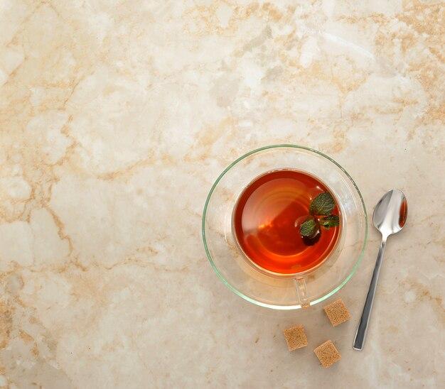 Herbata w przezroczystym szklanym kubku ze spodkiem i krajalnicami do trzciny cukrowej