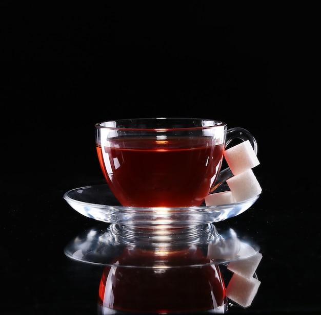 Herbata w szklanej filiżance na ciemnym tle z cukrem