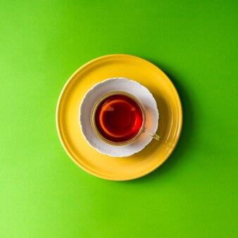Herbata w szklanej filiżance na zielonej ścianie. leżał na płasko.