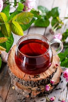 Herbata w szklanej filiżance z płatkami róż i świeżymi kwiatami na podłoże drewniane
