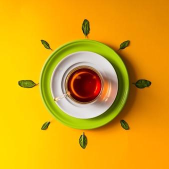 Herbata w szklanej filiżance z zielonymi liśćmi na pomarańczowej ścianie. pojęcie czasu.