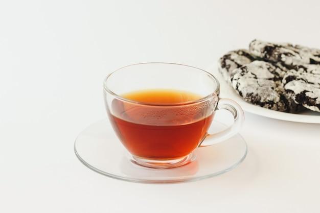 Herbata w szklanym kubku i domowe ciasteczka na białym tle