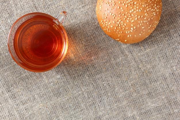 Herbata w szklanym kubku i sezamowej bułce na płótnie obrusie. widok z góry.