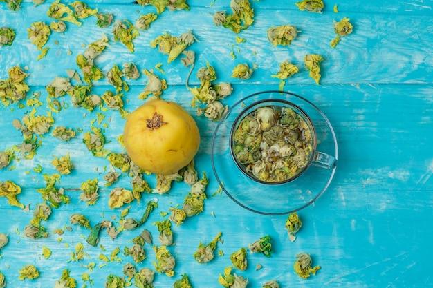 Herbata w szklanym kubku z suszonymi ziołami, pigwa na niebieskim drewnie