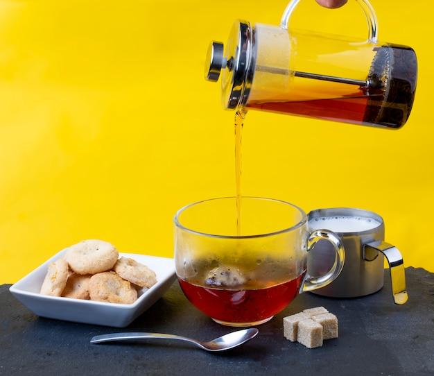 Herbata wlewa się do filiżanki na stole w kuchni