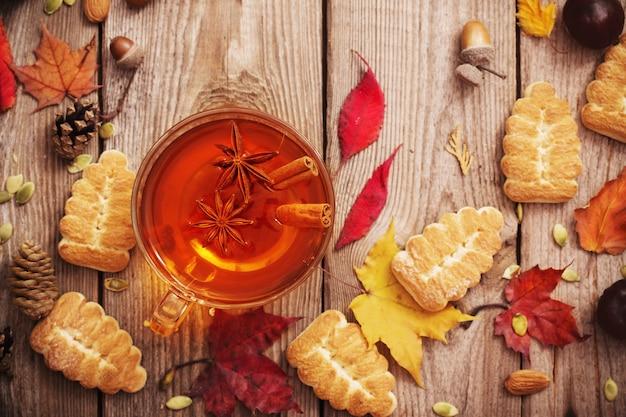 Herbata z ciasteczkami i jesiennymi liśćmi na starym drewnianym