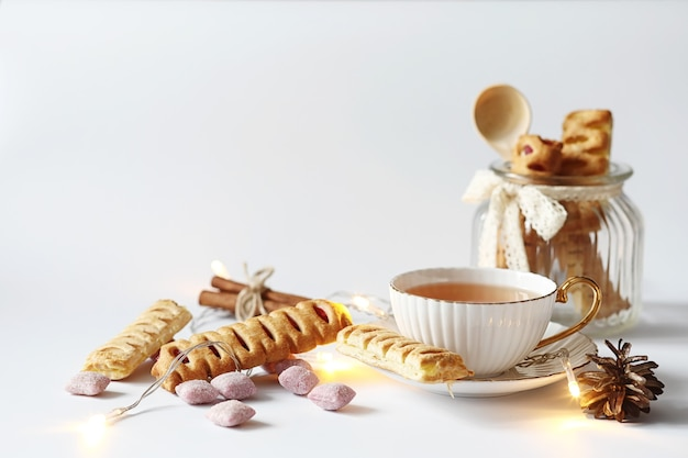 Herbata z ciastkami na śniadanie. słodycze i ciastka z orzechami na herbatę na białym tle. filiżanka kawy i paszteciki.