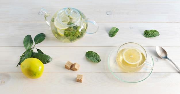 Herbata z cytryną i mennicą w szklanym zbiorniku na białym tle