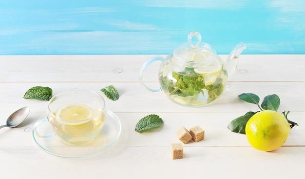 Herbata z cytryną i mennicą w szklanym zbiorniku na drewnianym tle
