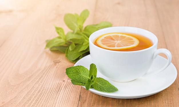 Herbata z cytryną i miętą na drewnianym stole