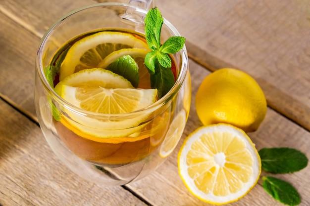 Herbata z cytryną i miętą w przezroczystej filiżance.