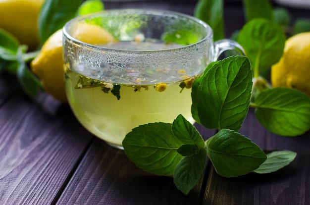 Herbata z cytryną i miętą w szklanej przezroczystej filiżance na stole