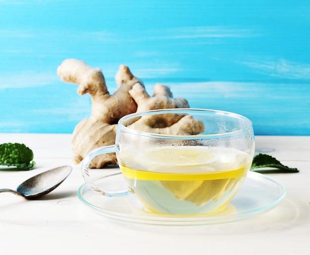 Herbata z cytryną i miętą w szklanym pojemniku w tle