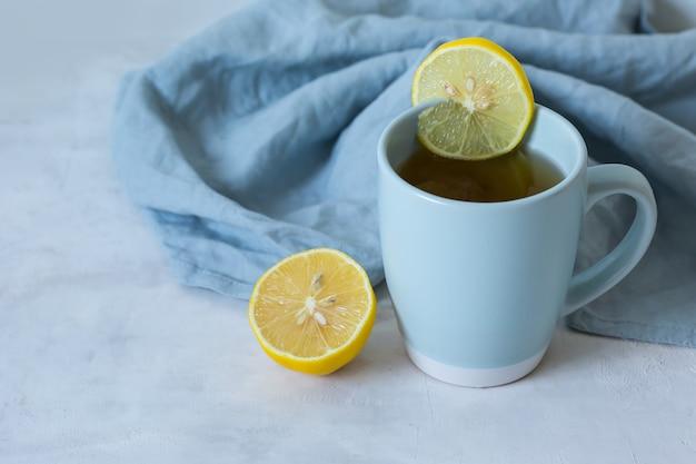 Herbata z cytryną w niebieskim kubku. środki ludowe do leczenia przeziębienia. organiczne leki na przeziębienie. naturalne środki na przeziębienia