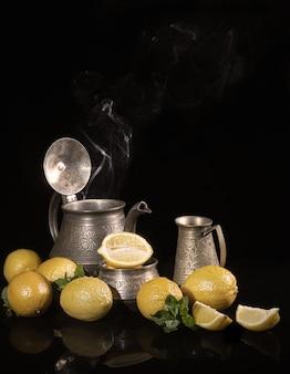 Herbata z cytrynami. martwa natura z cytryn i metalowych naczyń, imbryk, dzbanek na mleko i cukiernica.