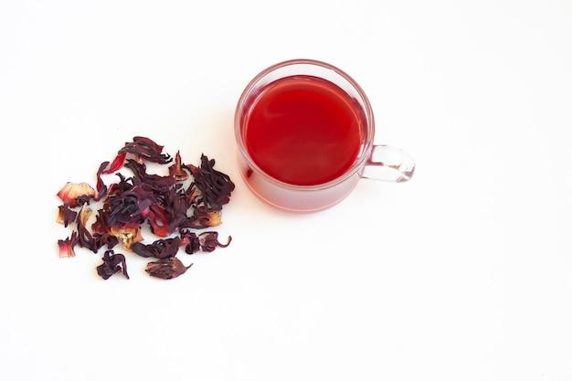 Herbata z czerwonego hibiskusa w szklanej przezroczystej filiżance i suszone kwiaty hibiskusa, widok z góry