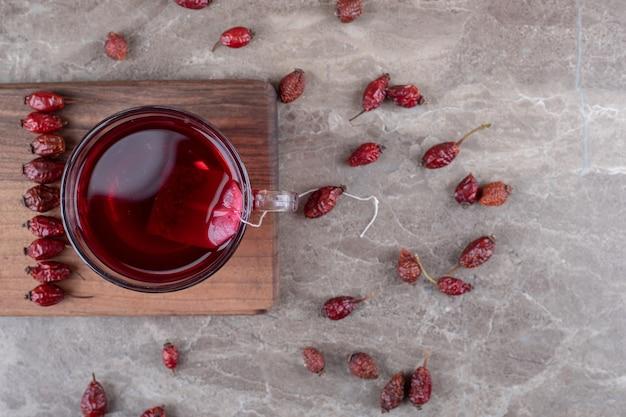Herbata z dzikiej róży i owoce dzikiej róży na pokładzie, na marmurowym tle.