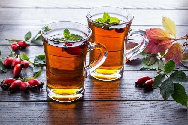 Herbata z dzikiej róży w przezroczystym kubku z miodem i świeżymi jagodami. napój witaminy c na ciemnym stole