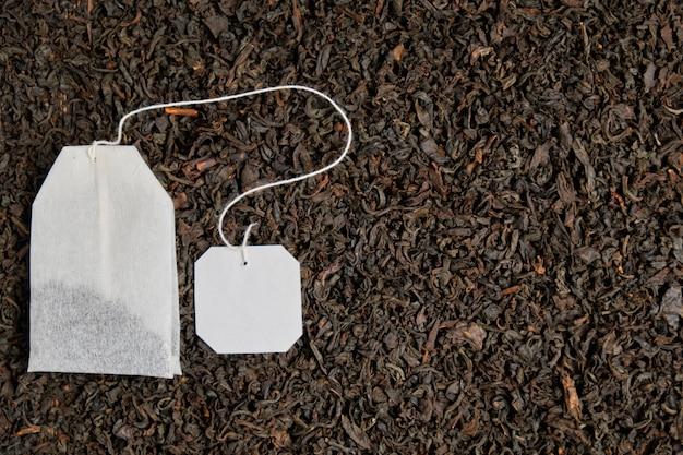 Herbata z etykietą na tle czarnej herbaty.