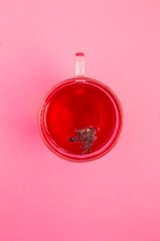 Herbata z hibiskusa lub karkade w szklanym kubku na różowym stole. widok z góry. skopiuj miejsce.