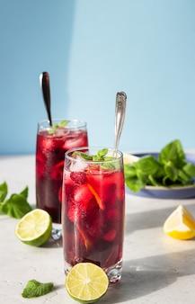 Herbata z hibiskusem, jagodami, miętą, cytrusami i lodem w słońcu z cieniami.