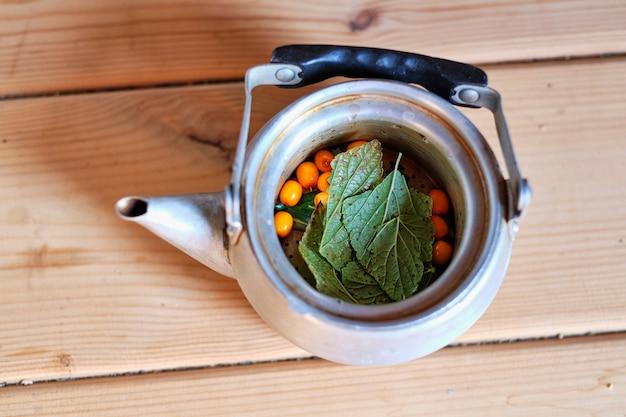 Herbata z jagodami rokitnika w żelaznym czajniczku na drewnianym tle, widok z góry, miejsce. sezonowa jesienna pikantna herbata z rokitnika.